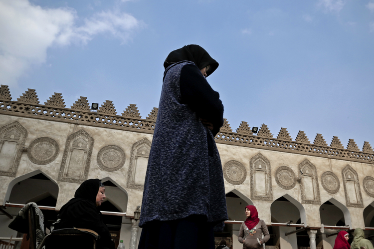 In this Feb. 20, 2017 file photo, an Indonesian al-Azhar university student, center, and an elderly Egyptian woman pray at al-Azhar Mosque, in Cairo, Egypt. (AP Photo/Nariman El-Mofty)