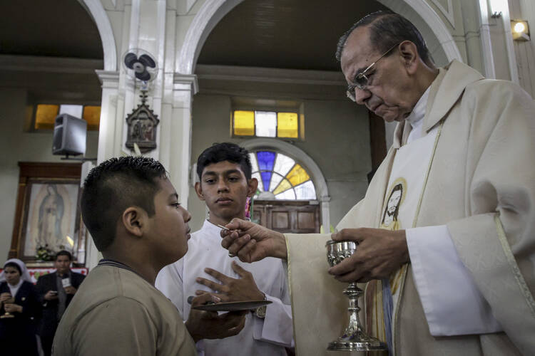 A youth takes the Eucharist from Monsignor Gregorio Rosa Chavez during a Mass giving thanks for Pope Francis' announcement that Chavez will be elevated to the rank of cardinal, at San Francisco de Asis parish church in San Salvador, El Salvador on Monday, May 22, 2017. (AP Photo/Salvador Melendez)