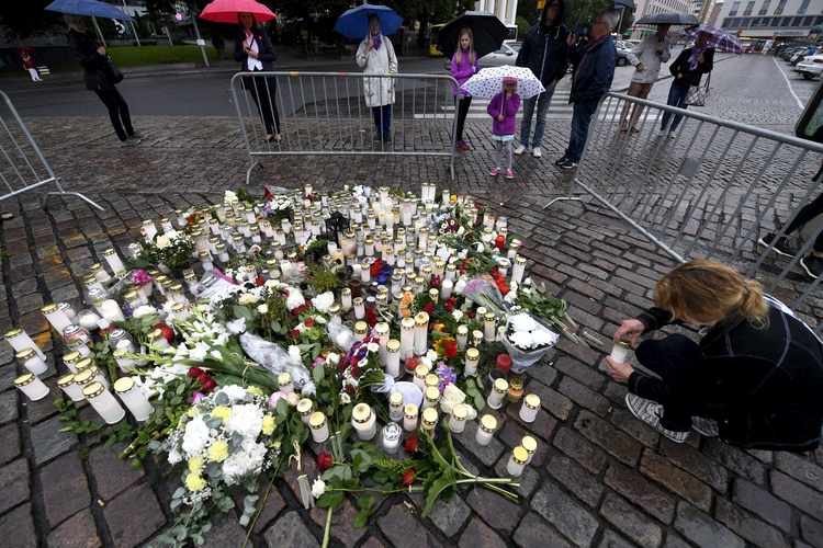 A woman places a candle by floral tributes for the victims of an attack at Turku Market Square on Friday, in Turku, Finland, Saturday, Aug. 19, 2017. (Vesa Moilanen/Lehtikuva via AP)