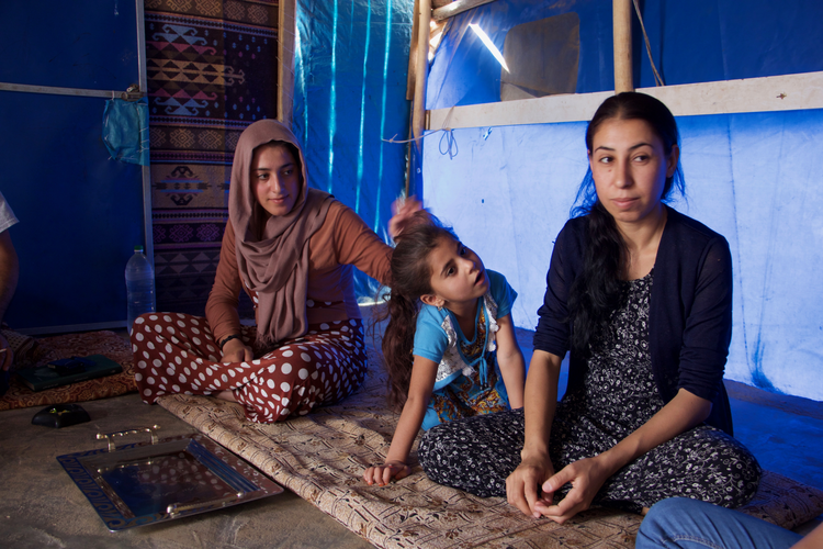 Image: Layla Taalo, far right, with her daughter and niece. All were captives of ISIS. Photo by Kevin Clarke.