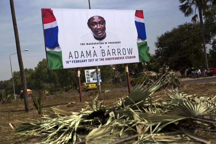 A billboard calling for the inauguration of Adam Barrow as president on Feb. 18 is set on the side of a road in Serrukunda, Gambia, on Jan. 27. Hundreds of thousands turned out on Jan. 26 to greet President Adama Barrow, a week after he took the oath of office in neighboring Senegal. (AP Photo/Jerome Delay)