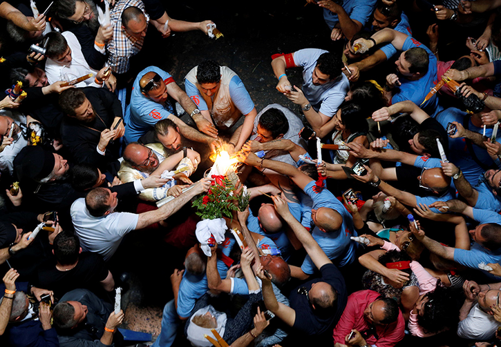 Worshippers light their candles as they take part in the Christian Orthodox Holy Fire ceremony at the Church of the Holy Sepulchre in Jerusalem's Old City on April 30, 2016. Photo courtesy of Reuters/Ammar Awad