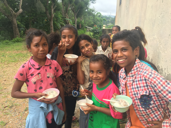 Feeding under nourished village children at Cocoa, East Timor.  Photo by Michael Sainsbury.