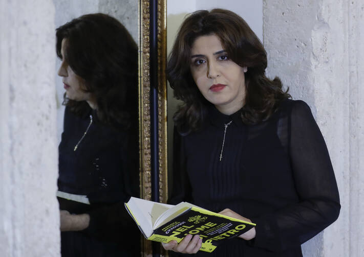 PR agent Francesca Chaouqui holds her book 'In the Name of Peter' (Nel Nome di Pietro), a behind-the-scenes drama of a papal reform commission, on Monday, Feb. 6, 2017. (AP Photo/Andrew Medichini)