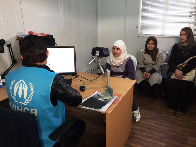 In this photo taken Sunday, Feb. 26, an 11-year-old Syrian refugee girl poses for a biometric iris scan in an interview room of the U.N. refugee agency in Amman, the first step in what are typically two years of interviews and background checks ahead of possible resettlement to the West, including the United States. (AP Photo/Karin Laub)