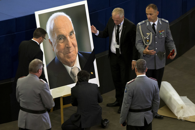 European Parliament employees set up a portrait of former German Chancellor Helmut Kohl before an European ceremony in Strasbourg on July 1. The ceremony was followed by a requiem Mass at the cathedral in Speyer, Germany. (AP Photo/Michel Euler)