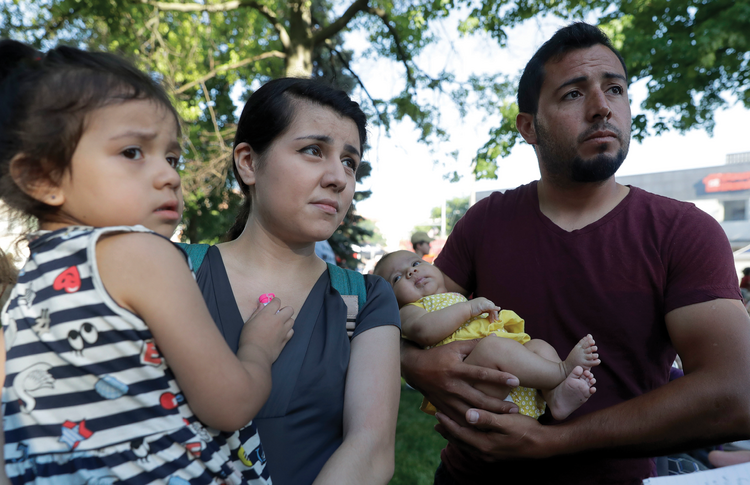Pepe Urzua, a roofer who arrived from Mexico eight years ago, cradles his two-month-old daughter, Luna, as his wife, Betty, holds their daughter, Scarlet, during the a street festival in Goshen, Ind., on June 1, 2018. (AP Photo/Charles Rex Arbogast)