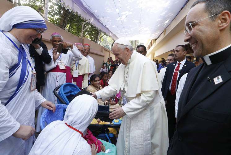 Pope Francis blesses people as he visits the Mother Teresa House