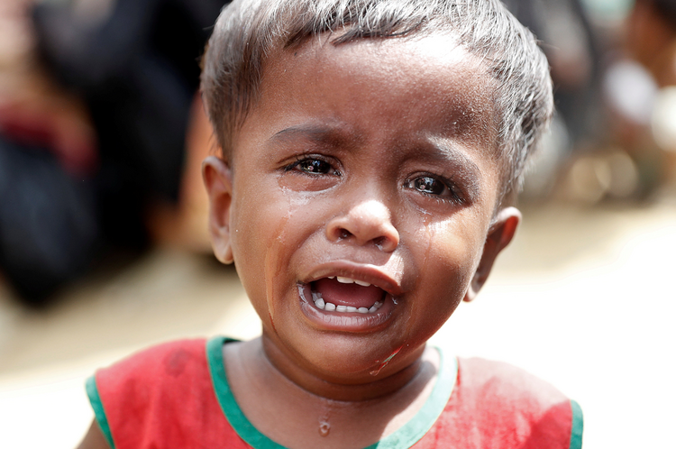 A Rohingya refugee child cries as others wait in line for aid Sept. 22 at a camp in Cox's Bazar, Bangladesh.