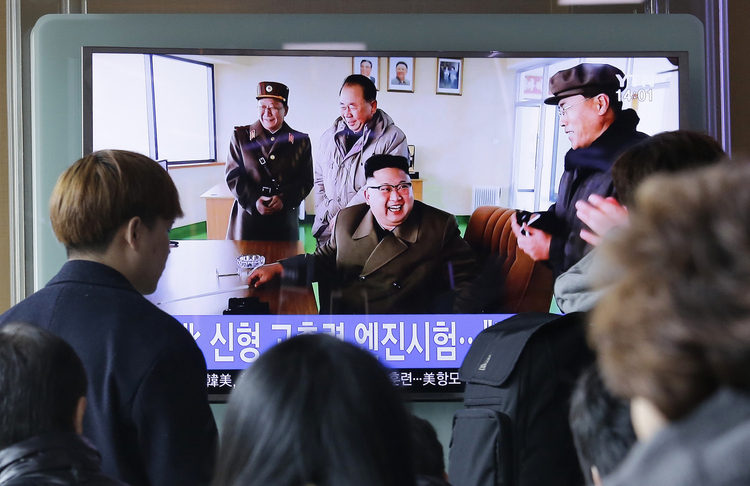 People watch a TV news program showing an image, published in North Korea's Rodong Sinmun newspaper, of North Korean leader Kim Jong Un at the country's Sohae launch site, at Seoul Railway station in Seoul, South Korea, on Sunday, March 19, 2017. (AP Photo/Ahn Young-joon)