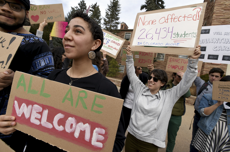 Gwendalynn Roebeke, left, is among dozens of people at a travel ban protest at the University of Colorado in Boulder on Thursday, Feb. 9, 2017. ( Cliff Grassmick/Daily Camera via AP)