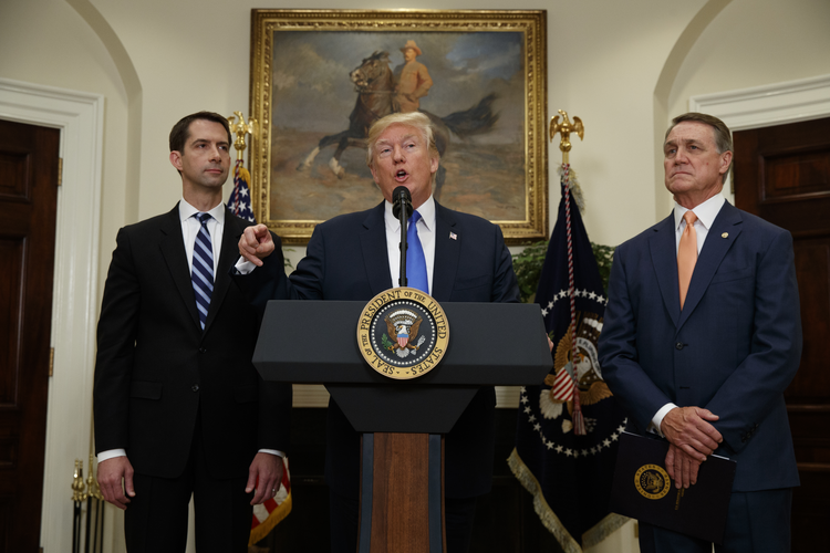 President Donald Trump, flanked by Sen. Tom Cotton, R- Ark., left, and Sen. David Perdue, R-Ga., speaks in the Roosevelt Room of the White House in Washington on Aug. 2, 2017, during the unveiling of legislation that would place new limits on legal immigration. (AP Photo/Evan Vucci)
