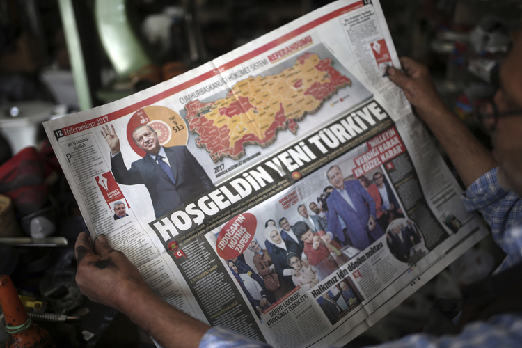 A man reads a newspaper with images of Turkey's President Recep Tayyip Erdogan and a map showing the results of Sunday referendum, in Diyarbakir, Turkey, on Monday, April 17, 2017. (AP Photo/Emre Tazegul)