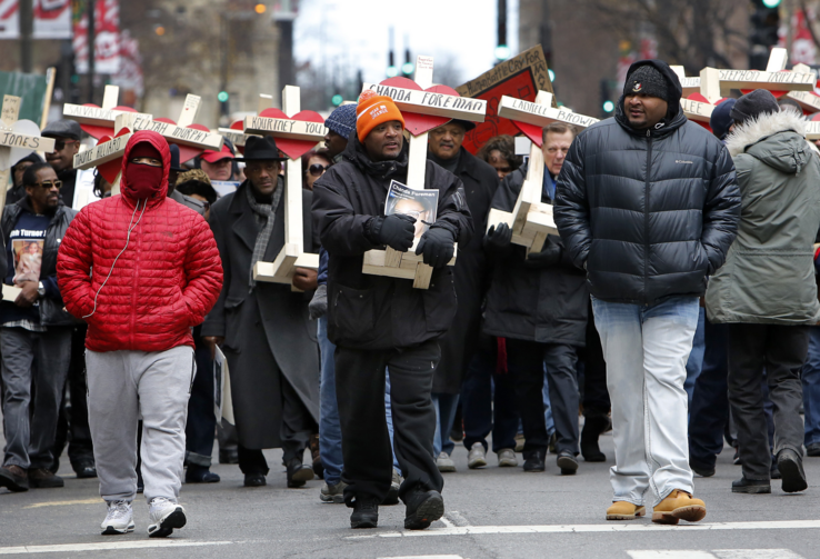 People carry crosses with names of victims of gun violence during a Dec. 31 march in downtown Chicago. Hundreds of people joined the march to remember those who died by gun violence in 2016 (CNS photo/Karen Callaway, Catholic New World).