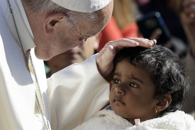 Pope Francis caresses a child as he arrives for his weekly general audience, at the Vatican, Wednesday, on March 29, 2017. (AP Photo/Andrew Medichini)