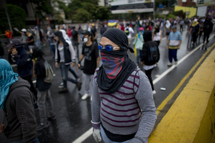 Demonstrators march on a highway as Bolivarian National Guard soldiers block their way during an anti-government protest in Caracas, Venezuela, Thursday, April 13, 2017. Venezuela officials are confirming that a fifth person has died in a two-week old anti-government protest movement. (AP Photo/Ariana Cubillos)