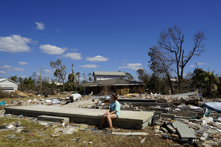 Caroline McClain, 16, sits on the ruins of her family's Mexico Beach vacation home after Hurricane Michael. Photo by Atena Sherry.