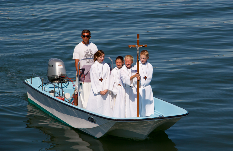 Altar servers from St. Mary of the Assumption at St. Ann's Church in Hull, Mass., approach a pier in August 2013 as part of a festival for the feast of the Assumption of Mary.
