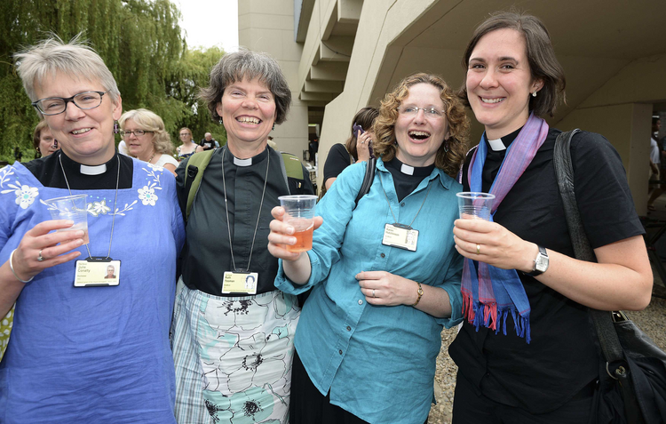 Women react after Church of England synod approves ordination of women bishops, July 14.