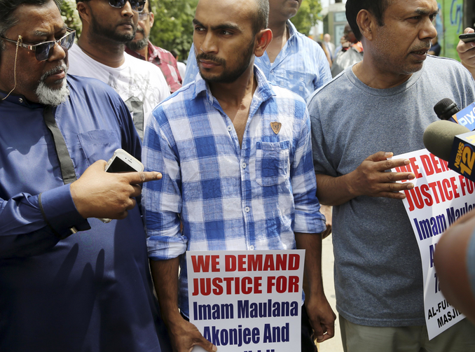 Saif Akonjee, son of Imam Maulana Alauddin Akonjee, center, Mashuk Uddin, brother of Thara Uddin, right, and other members of the community are surrounded by reporters as they arrives to a Queens courthouse in New York, on Aug. 16. (AP Photo/Seth Wenig)
