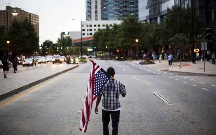 Skylar Barrett walks with an American flag in the middle of the street during a march through the Buckhead neighborhood against the recent police shootings of African-Americans on Monday, July 11, 2016, in Atlanta. (AP Photo/David Goldman)