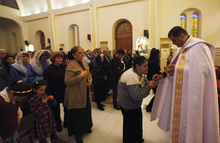 A priest gives Communion during Mass at a church in Baghdad March 1. Christian organizations have begun funneling aid to Syrian cities that are housing refugees from the Islamic State. (CNS photo/Ahmed Saad, Reuters)
