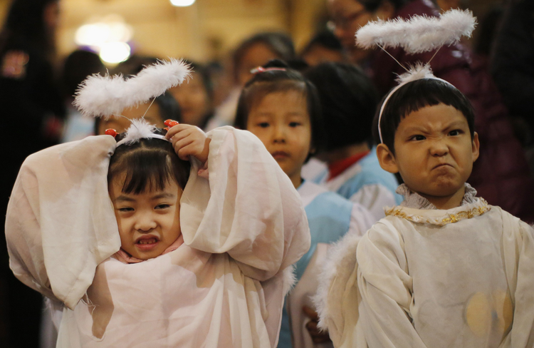 Children dressed as angels react as they attend Christmas Mass at Catholic church in Beijing, December 24.