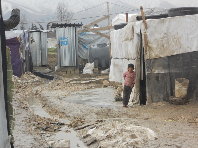 A Syrian child stands barefoot outside a tent Feb. 17 at a camp in Lebanon's Bekaa Valley. This winter's heavy rains have caused the paths between the tents at the settlements to fill with water. (CNS photo/Brooke Anderson)