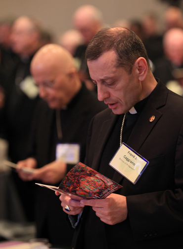 Bishop Frank J. Caggiano of Bridgeport, Conn., reads from booklet during the opening prayer of the annual spring meeting of the U.S. Conference of Catholic Bishops in New Orleans June 11, 2014. (CNS photo/Bob Roller)