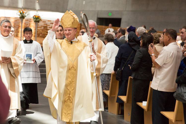 Bishop Michael C. Barber waves to the congregation after being installed as the fifth bishop of the Diocese of Oakland, Calif., May 25, 2013, at the Cathedral of Christ the Light. The 58-year-old Jesuit priest was previously the director of spiritual formation at St. John's Seminary in Brighton, Mass. (CNS photo/Jose Luis Aguirre, The Catholic Voice)