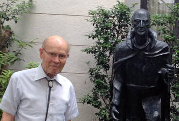 Bob Deiters, S.J. standing next to a statue of St. Ignatius in the courtyard of the Jesuit residence at Sophia University in Tokyo.