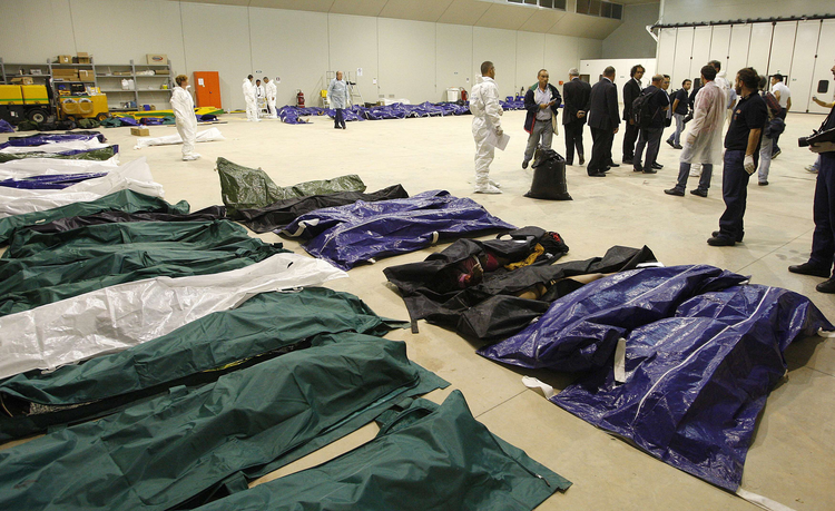 The bodies of African migrants lie in a hangar of the Lampedusa airport