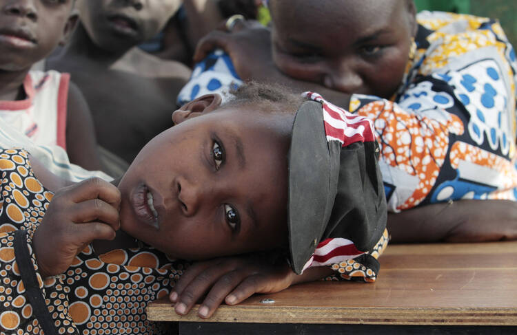 Girl displaced as a result of Boko Haram attack in Nigeria rests her head on desk at camp for displaced people, Jan. 20, 2015 (CNS photo/Afolabi Sotunde, Reuters).
