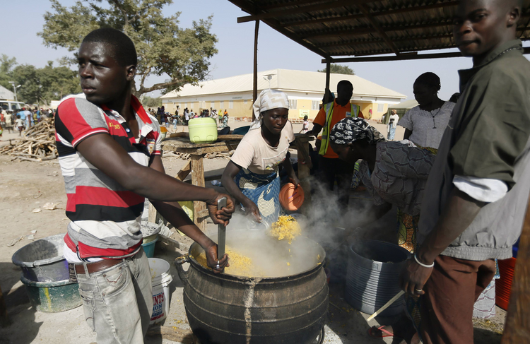 People fleeing Boko Haram violence in the northeast region of Nigeria cook food at a camp for internally displaced people in Yola Jan. 13. (CNS photo/Afolabi Sotunde, Reuters)