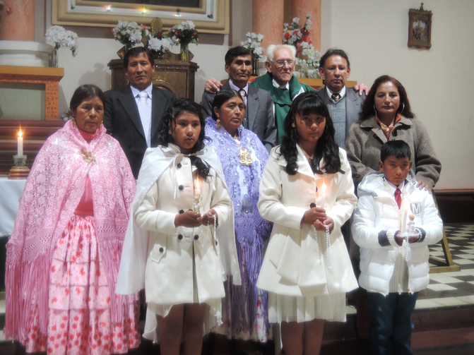 Father Sebastian Obermaier poses for a photo with three children and their families after a baptism in El Alto, Bolivia, July 4. (CNS photo/David Agren)