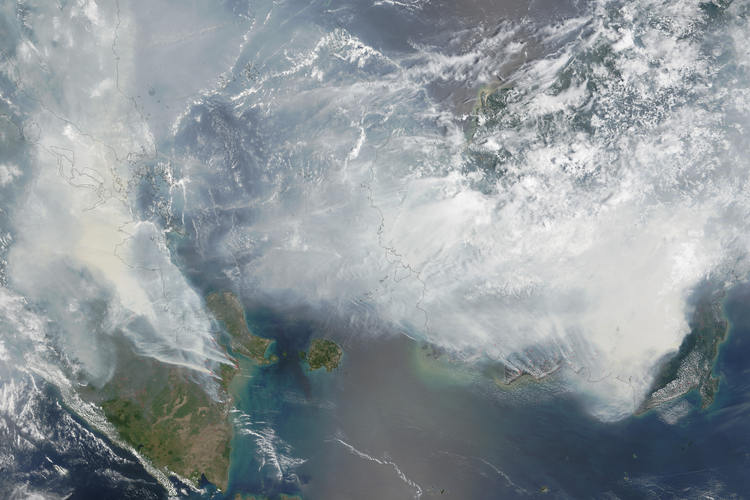 In this NASA image smoke rises from hundreds of active fires across Borneo and Sumatra.
