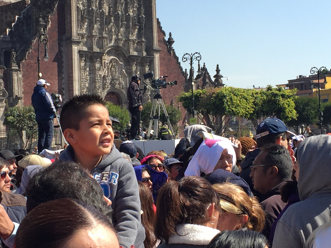 Watching Francis. A young boy with the crowd in Mexico City's historic Zocalo watches Pope Francis on a jumbo screen as he speaks to Mexico's bishops on Feb. 13. (Photo by Kevin Clarke)