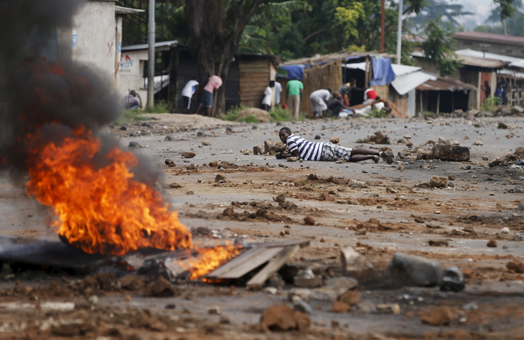 Demonstrators in Bujumbura, Burundi, take cover during a May 20 protest against President Pierre Nkurunziza and his bid for re-election. (CNS photo/Goran Tomasevic, Reuters)