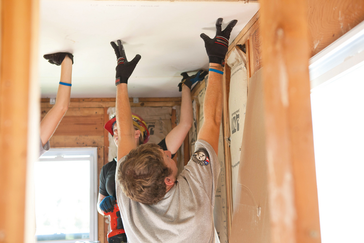 HELPING HANDS. AmeriCorps members put up dry wall after the tornado in Joplin, Mo