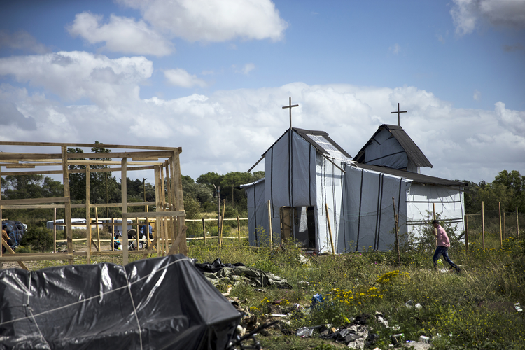 "A migrant walks past a makeshift church in the ""Jungle"" camp in France (CNS photo/Etienne Laurent, EPA)."