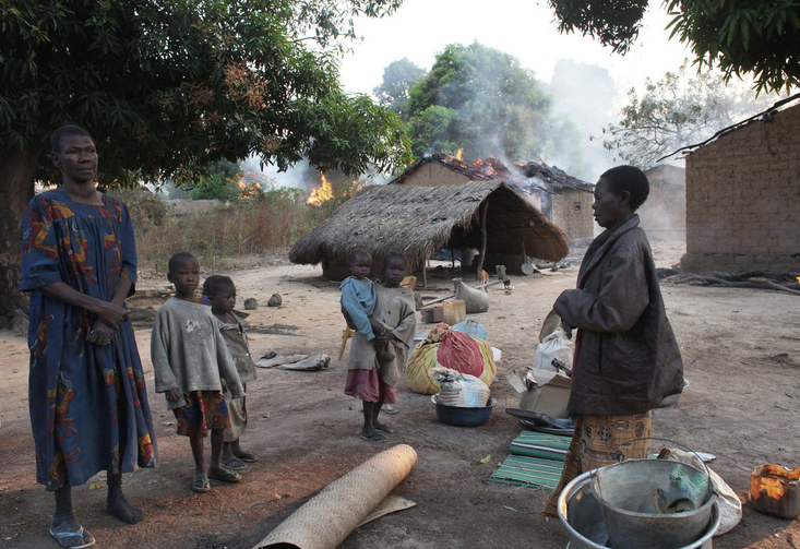 Women and children stand near their destroyed house in a village in Bossangoa, Central African Republic