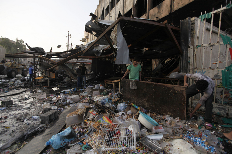 People gather at the site of an Oct. 2 car bomb attack that killed 11 people in Baghdad. (CNS photo/Ahmed Saad, Reuters)