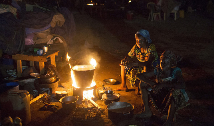 Displaced Muslim women prepare food next to their belongings in Bangui, Central African Republic.