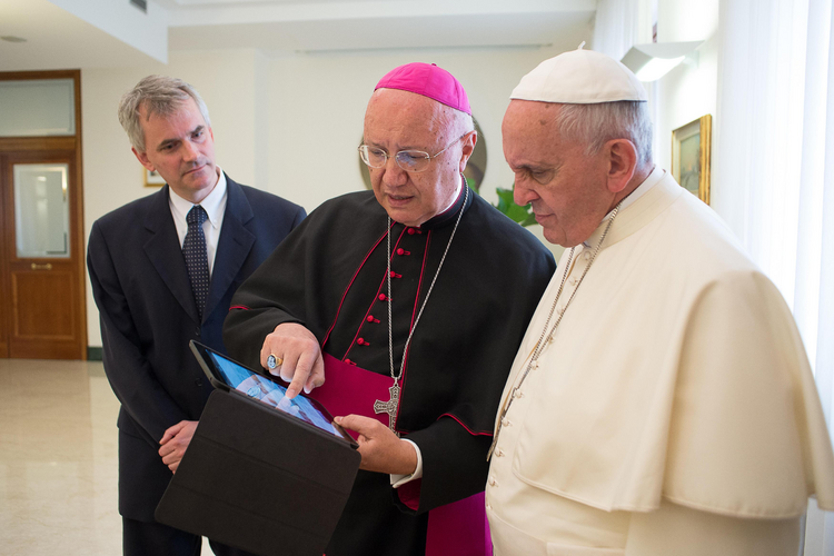 Archbishop Claudio Celli, president of the Pontifical Council for Social Communications, center, shows Pope Francis news on a tablet during a meeting at the Vatican on July 7.