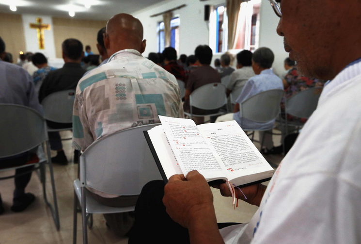 A man reads from a missal during Mass in a makeshift Catholic chapel in a village outside Tianjin, China, July 2012.
