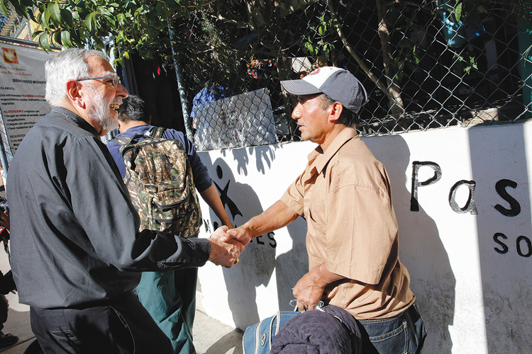 CARE OF SOULS. Bishop Gerald F. Kicanas of Tucson greets men entering a soup kitchen in Nogales, in northern Mexico, in 2014.