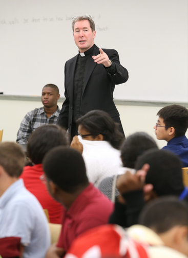 Jesuit Father James Van Dyke, principal of Cristo Rey Atlanta Jesuit High School, addresses students during an orientation, August 2014.