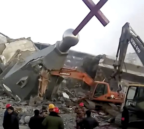 In this image taken from a video shot on Jan. 9, 2018, by China Aid and provided to the Associated Press, people in hard hats stand amid the remains of the Golden Lampstand Church in Linfen in northern China's Shanxi province. (China Aid via AP)