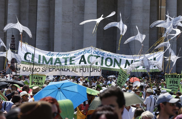 A banner calling attention to climate change in St. Peter's Square at the Vatican on June 28 when some 1,500 people marched to the Vatican in support of Pope Francis' encyclical on the environment. (CNS photo/Paul Haring)