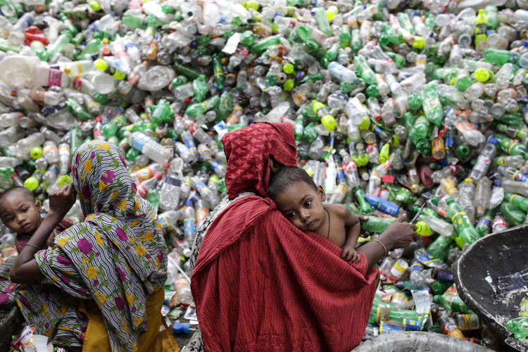 Women hold children while sifting through plastic bottles at a recycling factory in Mohammadpur, Bangladesh, Oct. 26. (CNS photo/Abir Abdullah, EPA)